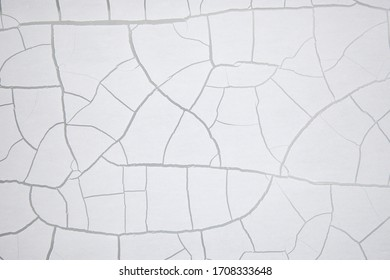 White old crackled paint on a wall. Crackle texture. Crackling abstract background.