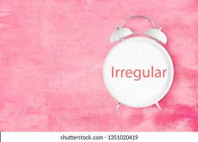 White old fashioned alarm clock with word Irregular on clock face on pink background. Irregular periods problem concept