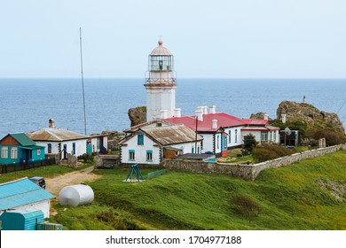 The white old lighthouse of the Gamov Cape, a village with dilapidated houses and green grass with clear blue sky and waves of the Peter the Great Gulf in the background, Russian Far East