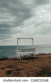 White old swing bench is on the edge of the cliff in front of blue lake. Swing bench out in the nature. The sky is grey.