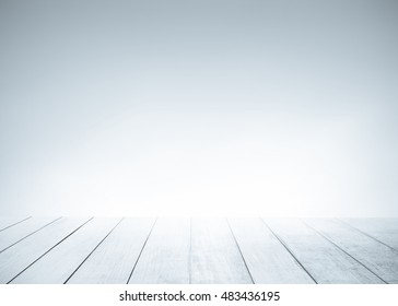 White old wood floor with blurred blue gray tone background. Wooden planks stage texture and blur flare sunlight. Abstract medical backdrop. Focus to table top in the foreground.