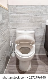 White one-piece toilet in a bathroom with cover in motion closing down