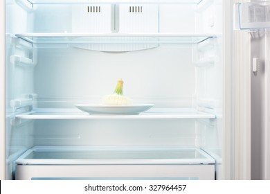 White onion on white plate in open empty refrigerator. Weight loss diet concept.