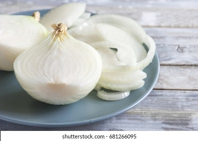 White onion on a wooden rustic table. Organic vegetables. Close-up of sliced raw organic white onion on a plate.