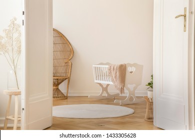 White open double door in elegant apartment with nursery designed with white crib and wicker peacock chair, real photo with copy space