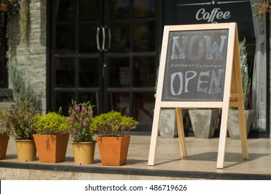 White 'Open' sign on black board with coffee cafe