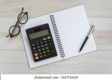 White opening blank paper note book with pen, calculator and eyeglasses on light grey wooden table background with copy space using as finance, debt and budget plan.