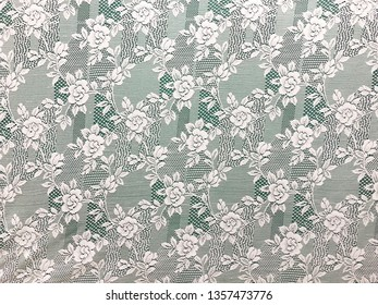 White openwork lace on green background.
