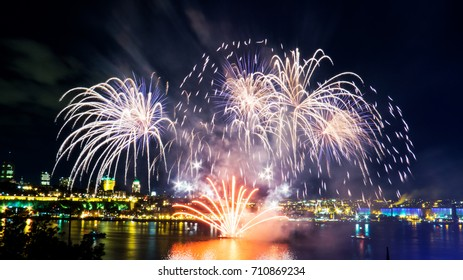 White and orange fireworks over the Saint-Lawrence River with a part of Quebec city in the background. Quebec, Canada.