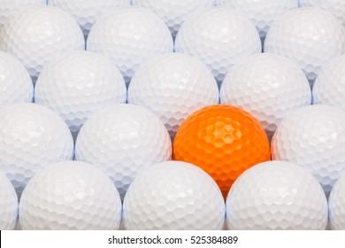 White and orange golf balls in the open box