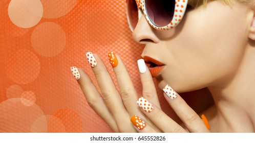 White orange manicure and makeup with a design of dots on female hand close up.
