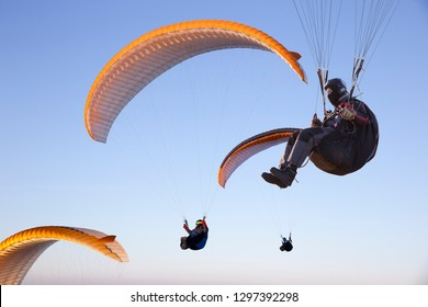 White orange paraglide with a paraglider in a cocoon against the background of fields of the sky and clouds. Paragliding Sports