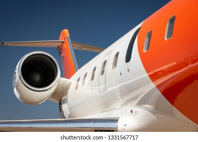 A white and orange private jet airplane against a blue sky