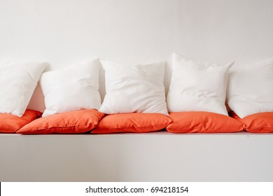 White and orange square pillows on white cozy seat sofa, flat image, blank copy space
