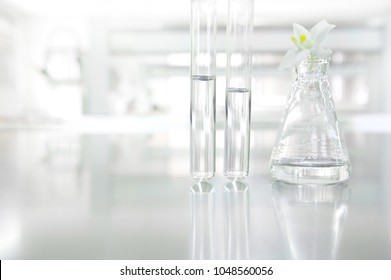white orchid flower on glass flask and test tube in science cosmetic biology laboratory background