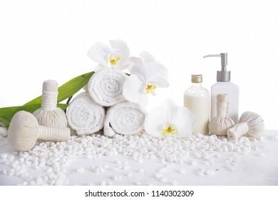 White orchid with rolled towel ,bottle oil with herbal ball ,leaf on pile of white stones