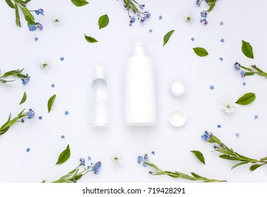 White organic pharmacy cosmetics flat lay with flowers and leaves. Clean beauty concept