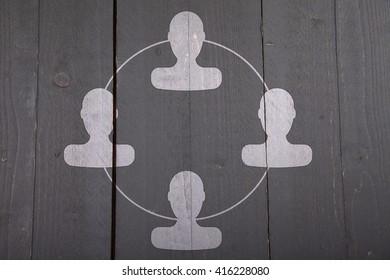 White organigram with white heads on dark black wooden background