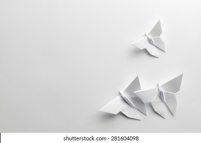 White origami butterflies on white background