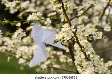 White origami dove bird hanging on blooming spring plum tree with variable focus