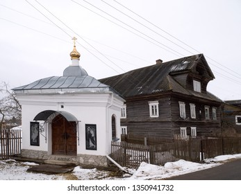 White orthodox chapel against old rural log house in Russia at winter season