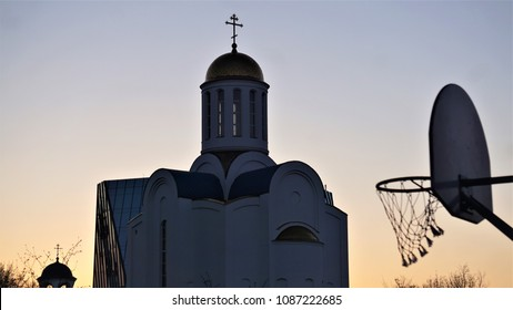White orthodox church in the evening. View from the playground with basketbal hoop.