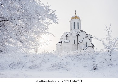 white Orthodox church with a golden dome on the background of branches with hoarfrost