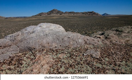 White outcrop of Metamorphic rock of Granite Mountains, Wyoming with blue sky and open prairie with sagebrush