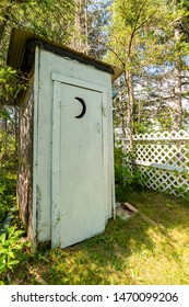 A white outhouse next to a small white wooden fence. A crescent moon is cut high in the door. Grass in front, and trees behind. The outhouse is in the shadows on a bright sunny day.