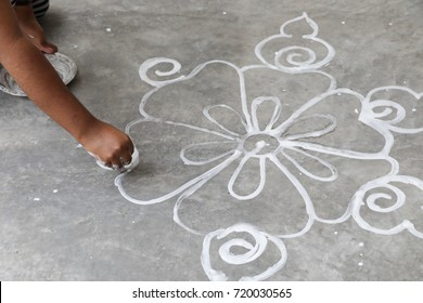 White outline of Kolam,Rangoli, Alpana or Chowk pujan being drawn by hand using rice flour on concrete floor in front of door