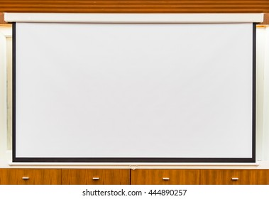 A white overhead projector on ceiling in meeting room.