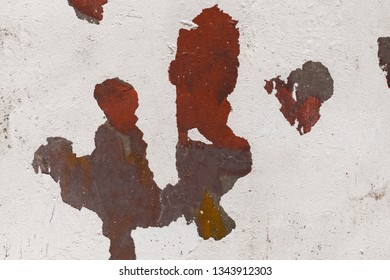 white paint slashes off the wall. Grungy cracked white wall paint peeling off. Texture, pattern, background. red and brown paint on a white wall