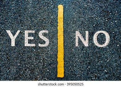 white paint yes or no message on the dark rough asphalt road with long grunge yellow