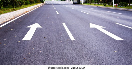 white painted arrow on black asphalt road