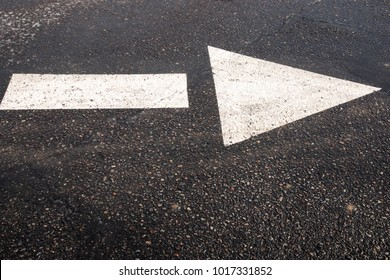 White painted arrow on wet black concrete