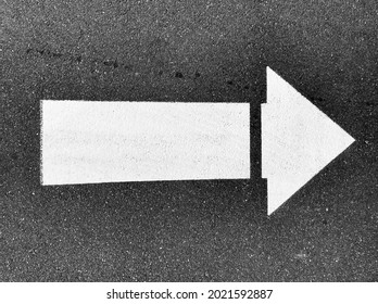 White painted arrow pointing in right direction (reversible for left) on black asphalt road