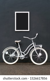 A white painted bicycle stands against a black wall. A white frame with a black empty space for inscriptions and pictures hangs on the wall. Minimalistic creative concept for creative ideas.