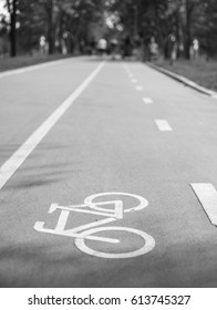 White painted bicycle way sign on asphalt in park.Separate cycling lane outdoor.Ride bike safe on bicycle road.Black & white photo
