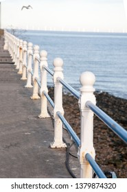 white painted bollards with blue railings creating the boundary on the walkway of an Edwardian pier, with the water one side, the pier on the other, stretching into the distance