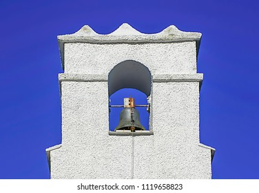 White painted chapel tower top with bell on beautiful, clean blue sky background.Historic architecture pearl in rural area of Cumbria,Uk.British countryside in spring.Lake District National Park.