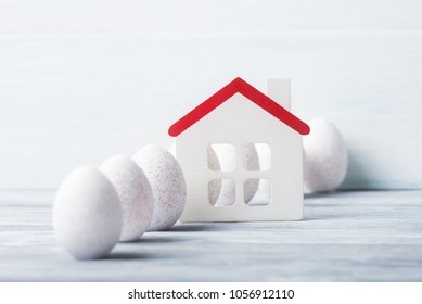 White painted Easter eggs and house model on wooden background.