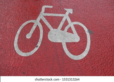 white painted icon for bicycle lane priority on red asphalt surface during rain storm