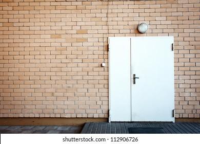 White painted metal door in a brick wall