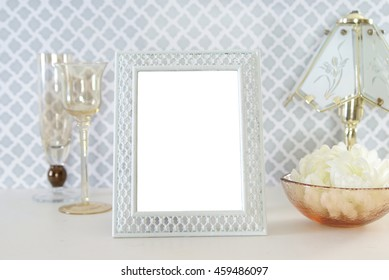 White painted photo frame surrounded by antique depression glass glassware with photo area cut out. Vintage or shabby chic style.