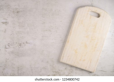 White painted pine wood cutting board  on white concrete background. Top view with copy space for text.