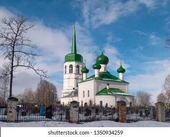 White painted Russian orthodox church with green roof and spike