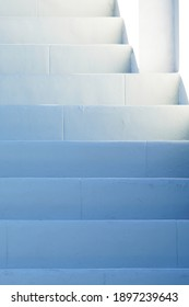 White painted stairs shaded in the blue afternoon light outside in the fresh air, getting lighter towards the top
