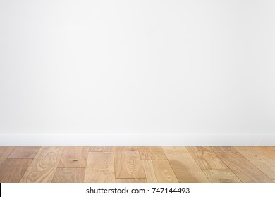 White painted stucco wall and natural wooden ash-tree 3-band parquet board hardwood floor. Flooring in scandinavian style of empty interior with wide white baseboards. Light brown, biscuit color.