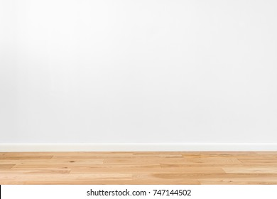 White painted stucco wall and natural wooden ash-tree 3-band parquet board hardwood floor. Flooring in scandinavian style of empty interior with wide white baseboards. Light brown, biscuit color