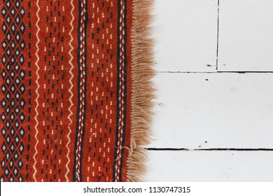 White Painted Wood Floor with an Orange Pattern Fringe Rug Perpendicular from the Side